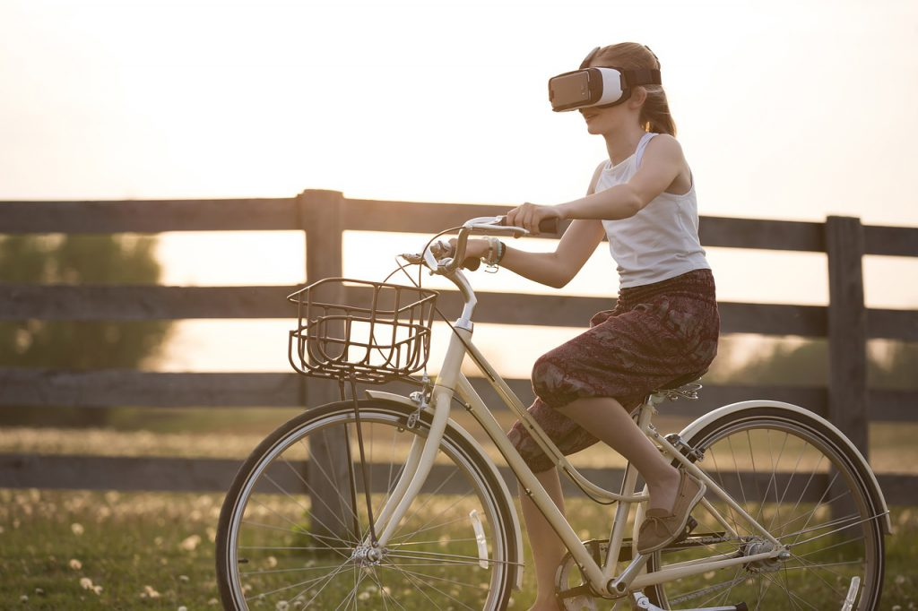 Girl wearing VR headset while riding a bike